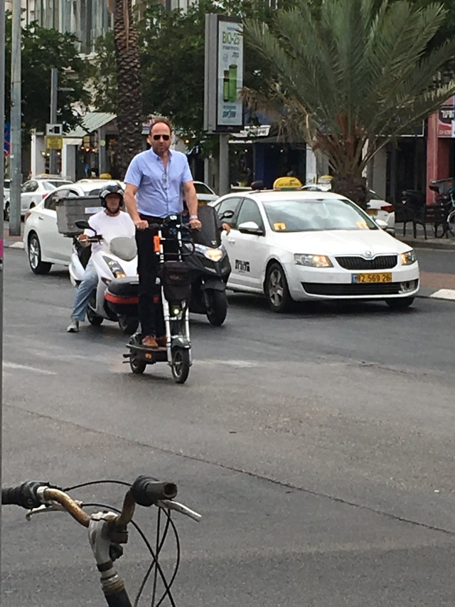 A man on a scooter in traffic. Tel Aviv. Brownell 2019